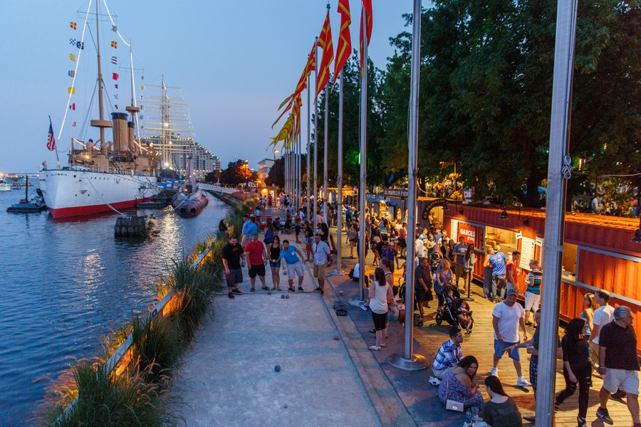 crowds walk on the boardwalk at spruce street harbor park